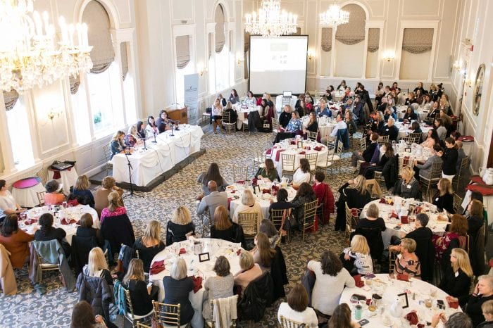 an aerial photograph of a panel discussion at a hotel with a large group of people